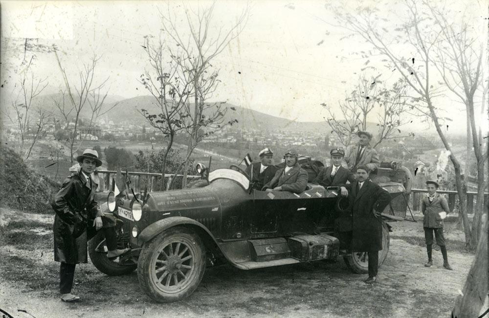 Екскурзијанти од Германија кои со своите автомобили поминале пет континенти. Милтон Манаки е потпрен на автомобилот десно. Тумбе Кафе Битола 1920/1921 година.